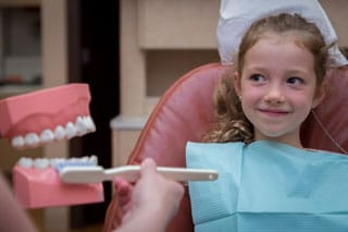 Children's Dentistry - image of little girl shown how to brush